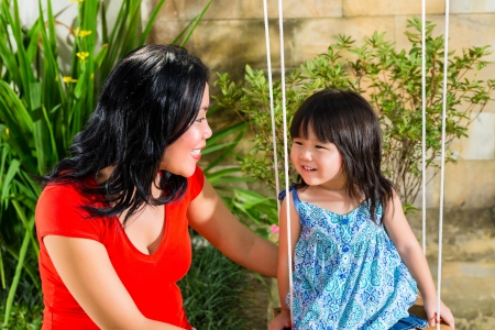 Indonesian Asian Little girl and her mother in the garden playing on a swing
