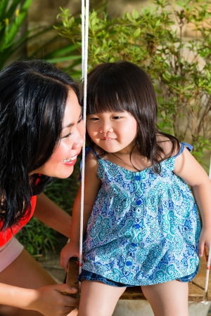 Indonesian Asian Little girl and her mother in the garden playing on a swing photo