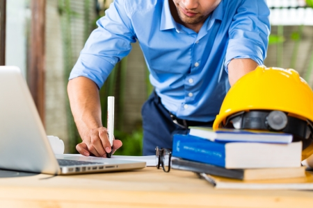 freelancing: Freelancer - Architect working at home on a design or draft, on his desk are books, a laptop and a helmet or hard hat Stock Photo