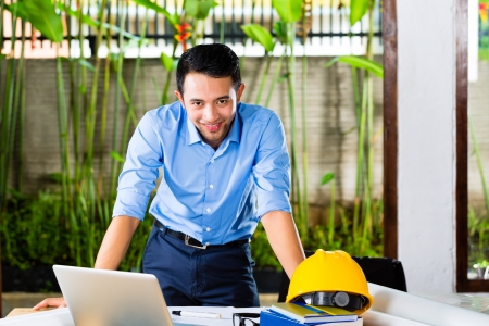 Freelancer - Architect working at home on a design or draft, on his desk are books, a laptop and a helmet or hard hat Stock Photo - 22110183