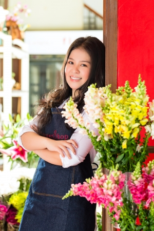likeable: Friendly Asian florist or Saleswoman in a flower shop
