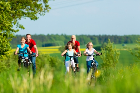 Familie mit drei M�dchen mit einen Wochenendausflug auf ihre Fahrr�der an einem Sommertag in sch�nen Landschaft
