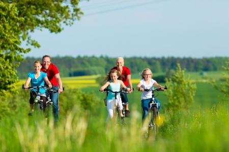 Famille avec trois jeunes filles ayant une excursion week-end sur leurs vélos sur une journée d'été dans un paysage magnifique