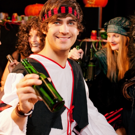 Group of young people celebrating a carnival or Halloween party in costumes drinking beer photo
