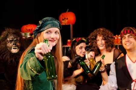カーニバルやビールを飲みながらの衣装でハロウィン パーティーを祝っている若い人たちのグループ