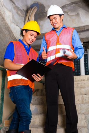 tallyman: Chinese supervisor or controller and worker or architect look on building site on a clipboard  Stock Photo