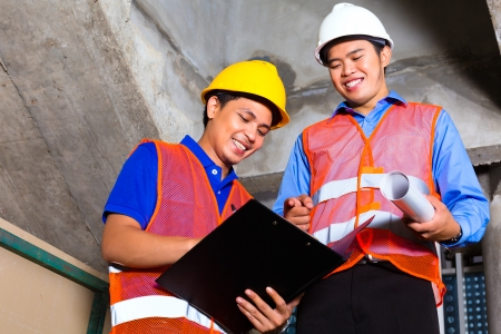 Chinese supervisor or controller and worker or architect look on building site on a clipboard Stock Photo - 22400182