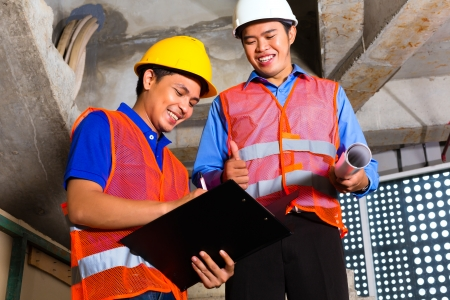 Chinese supervisor or controller and worker or architect look on building site on a clipboard  Stock Photo - 22400183