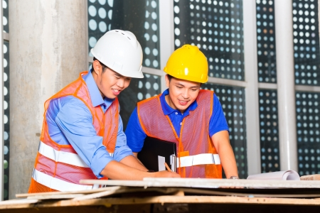 Chinese architect and supervisor point on building site on a construction plan Stock Photo - 22400184