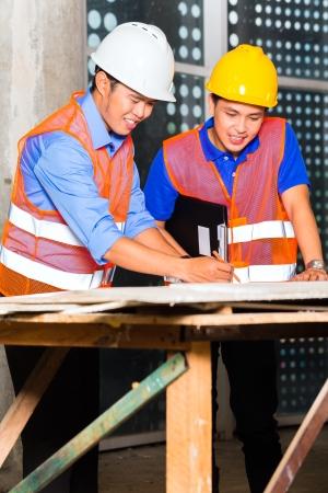 arquitecto: Arquitecto chino y el punto supervisor del sitio de construcci�n de un plan de construcci�n Foto de archivo