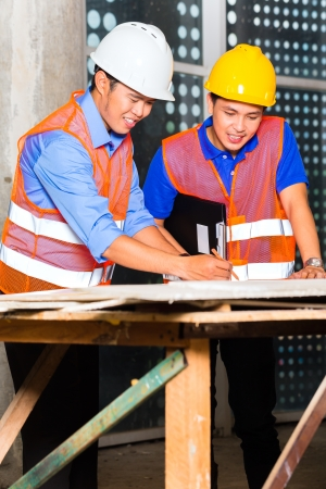 Chinese architect and supervisor point on building site on a construction plan photo