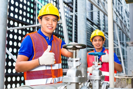 assistant engineer: Two technicians or engineers working on a valve on building technical equipment or industrial site