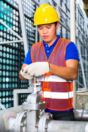 technician or engineer working on a valve on building technical equipment or industrial site Stock Photo - 22400187