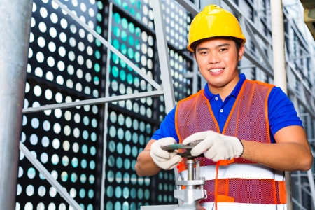technician or engineer working on a valve on building technical equipment or industrial site  Stock Photo - 22400188