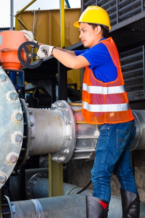 technician or engineer working on a valve on building technical equipment or industrial site in factory or utility photo