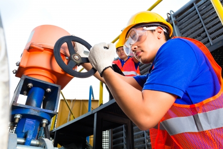 In utility or factory ewo technicians or engineers working on a valve on building technical equipment or industrial site Stock Photo - 22400191