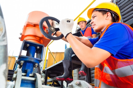 In utility or factory ewo technicians or engineers working on a valve on building technical equipment or industrial site Stock Photo - 22400192