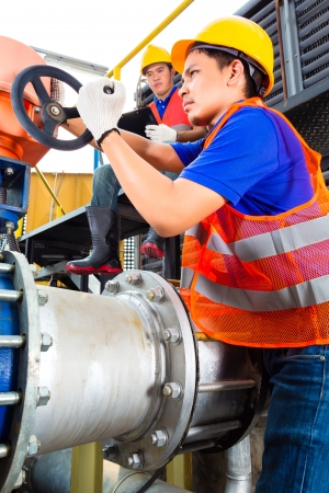 In utility or factory ewo technicians or engineers working on a valve on building technical equipment or industrial site  Stock Photo - 22400193