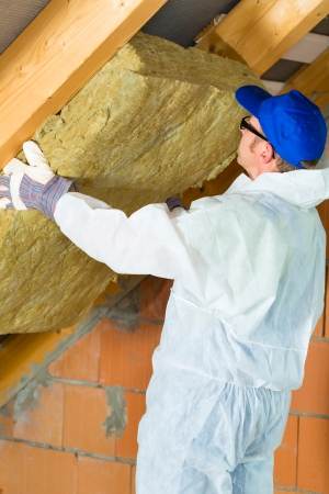 insulant: Worker in overall is setting thermal insulating material with gloves in the roof