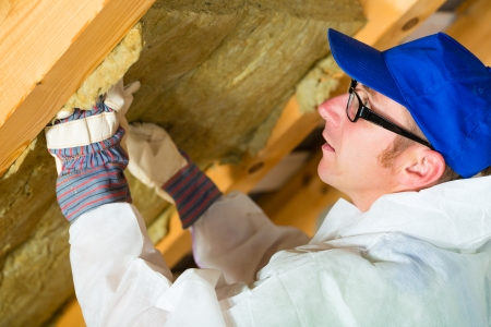 Worker in overall is setting thermal insulating material with gloves in the roof photo