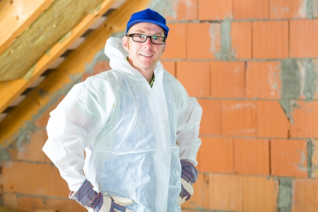 tallyman: Worker in overall doing construction the roof with thermal insulating material