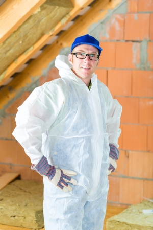 Worker in overall doing construction the roof with thermal insulating material  photo