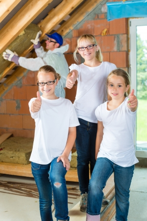 homeowners: Engineer or father with daughters or daughter with friends building the roof with insulating material