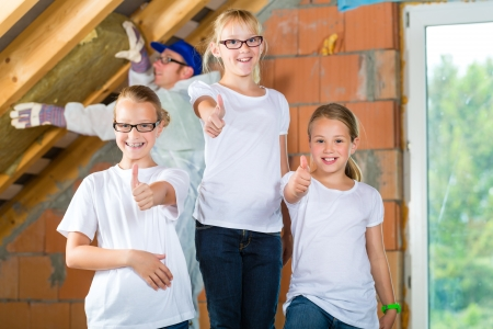 Engineer or father with daughters or daughter with friends building the roof with insulating material photo
