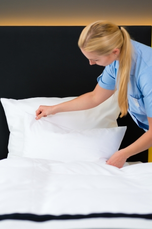 room service: Room service - young chambermaid changing the bedding or bedclothes in a hotel room