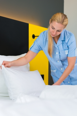 bedclothes: Room service - young chambermaid changing the bedding or bedclothes in a hotel room