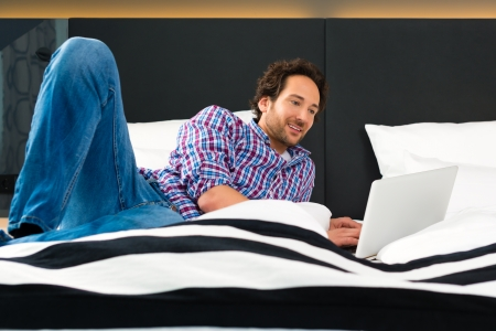 kingsize: Young man lying in the bed of a hotel room, suite, he are on vacation and using the wifi in the room for internet with the computer Stock Photo