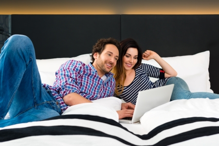kingsize: Young Couple lying in the bed of a hotel room, they are on vacation and using the wifi in the room for internet with the computer