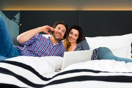 man in suite: Young Couple lying in the bed of a hotel room, suite, they are on vacation and using the wifi in the room for internet with the computer
