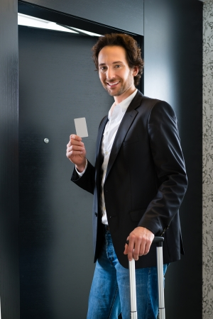Young business man standing with a keycard in front of a room door in a hotel photo