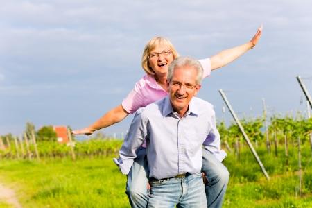 ancianos caminando: El hombre y la mujer, pareja de alto nivel, con un paseo en el verano o al aire libre en el viñedo