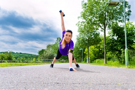 greenfield: Urban sports - young woman is doing warming up before running in the greenfield on a summer day Stock Photo