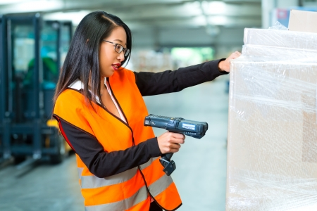 barcode scanner: Logistics - female worker or shipper with protective vest and scanner, scans bar-code of package, he standing at warehouse of freight forwarding company