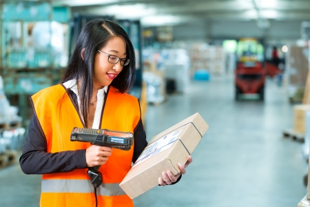 shipper: Logistics - female worker or shipper with protective vest and scanner, scans bar-code of package, he standing at warehouse of freight forwarding company