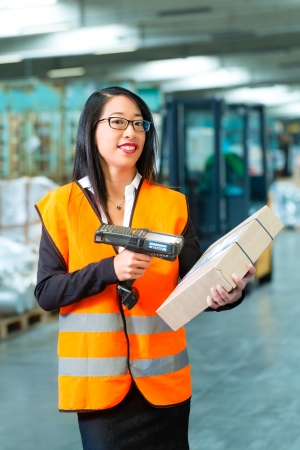 Logistics - female worker or shipper with protective vest and scanner, scans bar-code of package, he standing at warehouse of freight forwarding company Stock Photo - 22400473