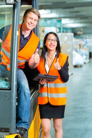 Logistics Teamwork - forklift driver, Worker or warehouseman and his coworker with tablet computer at warehouse of freight forwarding company photo