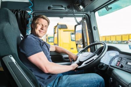 řidič: Logistika - hrdý řidič nebo dopravce v ovladači čepici nákladních automobilů a tahačů, na překladiště