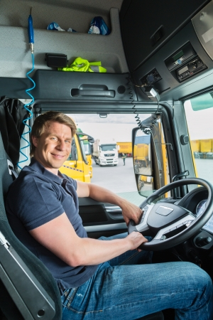 forwarder: Logistics - proud driver or forwarder in drivers cap of truck and trailer, on a transshipment point