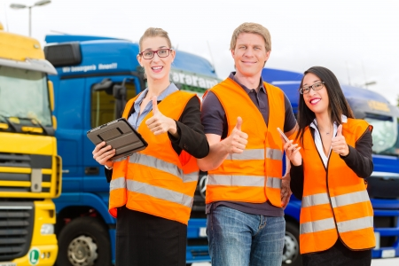 delivery driver: Logistics - proud driver or forwarder and colleagues with tablet computer, in front of trucks and trailers, on a transshipment point, its a good and successful team Stock Photo