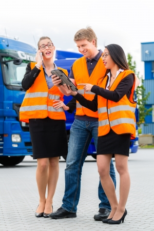 safety vest: Logistics - proud driver or forwarder and colleagues with tablet computer, in front of trucks and trailers, on a transshipment point, its a good and successful team Stock Photo