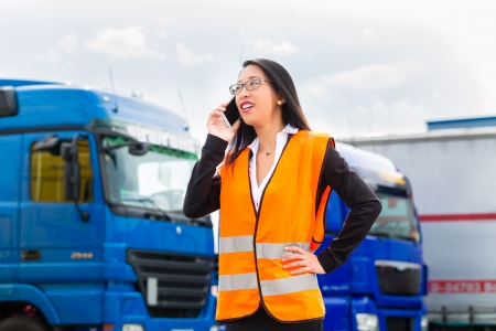 forwarder: Logistics - female Asian forwarder or supervisor with mobile phone, in front of trucks and trailers, on transshipment point