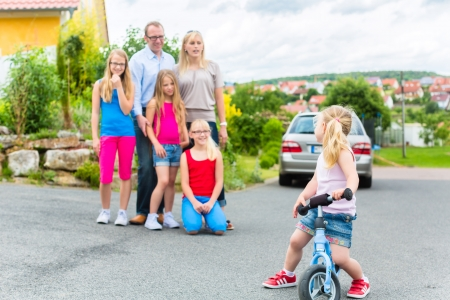 Young family with Mother, father and daughters standing in front of home in housing estate Stock Photo
