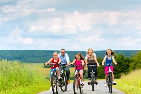 Gezin met drie meisjes die een weekend excursie op hun fietsen op een zomerse dag in het mooie landschap
