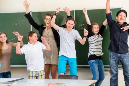 escuela primaria: Profesor y estudiantes con éxito saltar delante de una pizarra con el trabajo de matemáticas en una escuela de clase o clase mientras lección