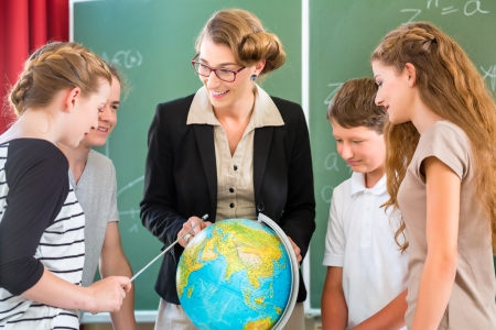 human geography: Students or pupils having group work while geography lesson and the teacher test or educate them in school or class