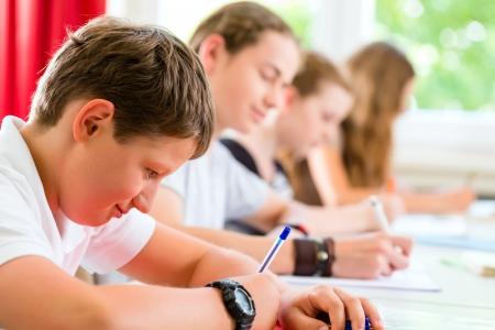 Los estudiantes o alumnos de clase de la escuela de escritura de un examen de la prueba en el salón de clases para concentrarse en su trabajo